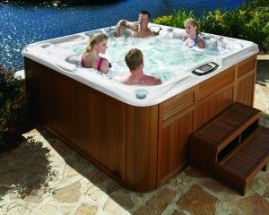Four people relaxing in a hot tub installed by the water.