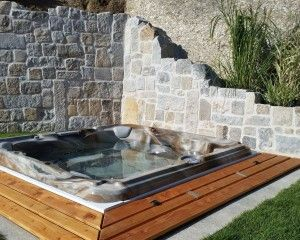 In-ground hot tub installation surrounded by stone masonry walls.