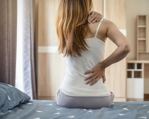 Woman sitting on the edge of the bed with back pain.a
