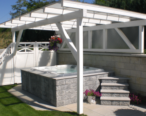 Sundance Spas hot tub under a white pergola built into a grey brick surround.